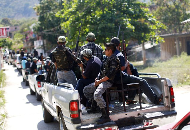 Members of the Community Police of the FUSDEG (United Front for the Security and Development of the State of Guerrero) ride with their weapons in the back of a vehicle to a celebration to mark the first anniversary of the force's operations in Ocotito, January 23, 2015. (Photo by Jorge Dan Lopez/Reuters)