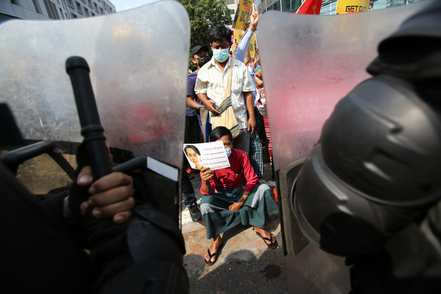 An anti-coup protester holds a poster with an image of deposed Myanmar leader Aung San Suu Kyi as he sits in front of riot police in Yangon, Myanmar Friday, February 19, 2021. The daily protests campaigning for civil disobedience in Myanmar are increasingly focusing on businesses and government institutions that sustain the economy. (Photo by AP Photo/Stringer)