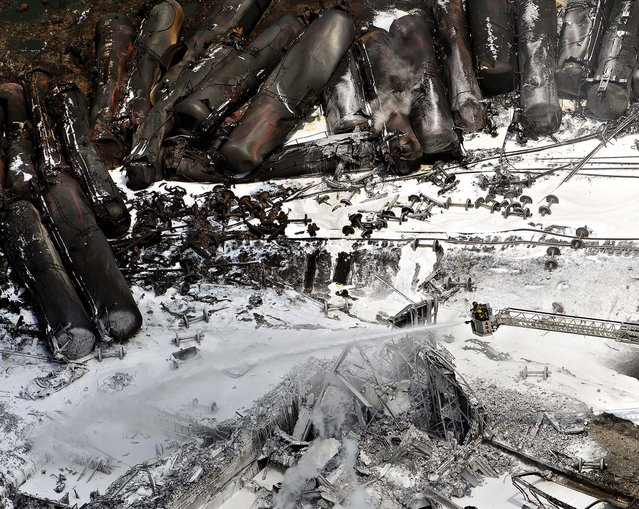 Firefighters continue to water smoldering rubble in Lac Megantic, Quebec. A runaway train derailed  Saturday igniting tanker cars carrying crude oil and killing at least five people. (Photo by Ryan Remiorz/The Canadian Press)