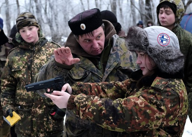An instructor guides a student from the General Yermolov Cadet School as she aims with a gun during a field exercise outside the south Russian city of Stavropol January 24, 2015. The General Yermolov Cadet School in Stavropol is a state-run institution that teaches military and patriotic classes in addition to a normal syllabus. (Photo by Eduard Korniyenko/Reuters)