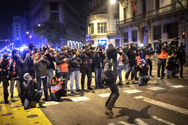 Media take images as a man throws a bottle agains a national police station during clashes following a protest condemning the arrest of rap singer Pablo Hasél in Barcelona, Spain, Sunday, February 21, 2021. (Photo by Emilio Morenatti/AP Photo)