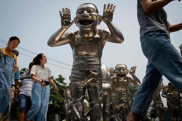 People walk passed sculptures by Chinese artist Minjun Yue on a street outside a museum in Beijing, China on July 5, 2018. (Photo by Nicolas Asfouri/AFP Photo)