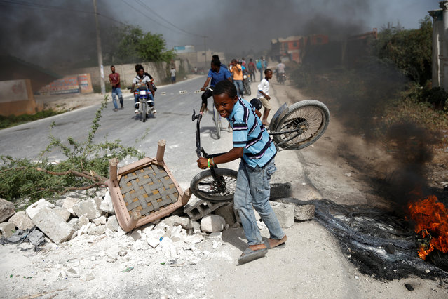 A boy carrying his bicycle passes through a barricade on the outskirts of Croix-des-Bouquets, Haiti, July 8, 2018. (Photo by Andres Martinez Casares/Reuters)