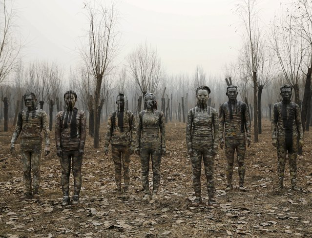 "Models painted in camouflage colours to blend in with the background pose for Chinese artist Liu Bolin's artwork ""Dongji"", or Winter Solstice, on the second day after China's capital Beijing issued its second ever ""red alert"" for air pollution, in Beijing, China, December 20, 2015. (Photo by Kim Kyung-Hoon/Reuters)"