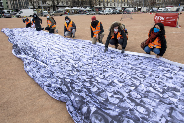 """Volunteers prepare the installation of the giant flag """"We are watching: The Eyes of the world"""" in Geneva, Switzerland, 06 March 2021. The flag was designed by artist Dan Acher and presented for first time during the COP25 UN Climate Change Conference in Madrid in 2019. It is depicting a monumental eye made up of thousands of portraits contributed from 190 countries, in the size of 10 storey building and was hoisted by a crane over the Plainpalais plain on 06 March. The flag is flying for the first time in Geneva in partnership with the FIFDH, International Film Festival and Forum on Human Rights, whose 2021 edition focuses on new forms of resistance. (Photo by Martial Trezzini/EPA/EFE)"""