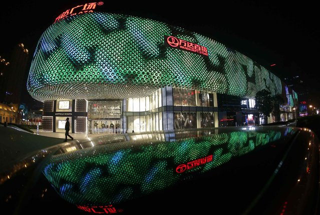 A man walks in front of an entrance to a Wanda Department Store in Wuhan, Hubei province December 23, 2014. The reflection is off the top of a car. (Photo by Reuters/Stringer)