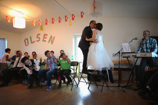 Newlyweds, Adam Olsen and Ottilie Olsen kiss as they stand on chairs in a hall in Qeqertaq, on July 20, 2013. (Photo by Joe Raedle/Getty Images via The Atlantic)