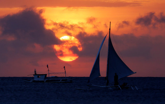 Tourists ride on a sailboat during sunset in Boracay in Philippines, April 8, 2018. (Photo by Erik De Castro/Reuters)