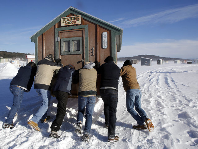 A wind gust whips up snow as a group of ice fishermen from Ashby, Mass., work to push their bob-house across frozen Lake Winnipesaukee, Thursday, February 5, 2015, in Meredith, N.H. Hundreds of fisherman are expected for the upcoming weekend's annual ice fishing derby. (Photo by Jim Cole/AP Photo)