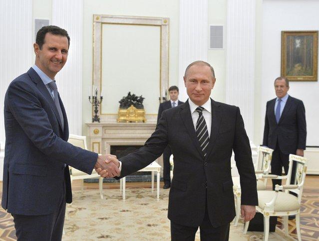 Russian President Vladimir Putin (R) shakes hands with Syrian President Bashar al-Assad during a meeting at the Kremlin in Moscow, Russia, October 20, 2015. (Photo by Alexei Druzhinin/Reuters/RIA Novosti/Kremlin)