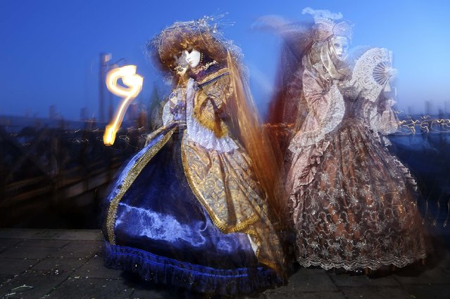Masked revellers pose in front of St. Mark's Square during the Venice Carnival, February 7, 2015. (Photo by Stefano Rellandini/Reuters)