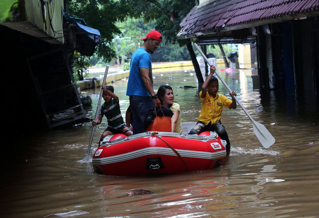 Residents use a rubber boat to make their way through a flooded neighborhood in Jakarta, Indonesia, Tuesday, February 10, 2015. (Photo by Tatan Syuflana/AP Photo)