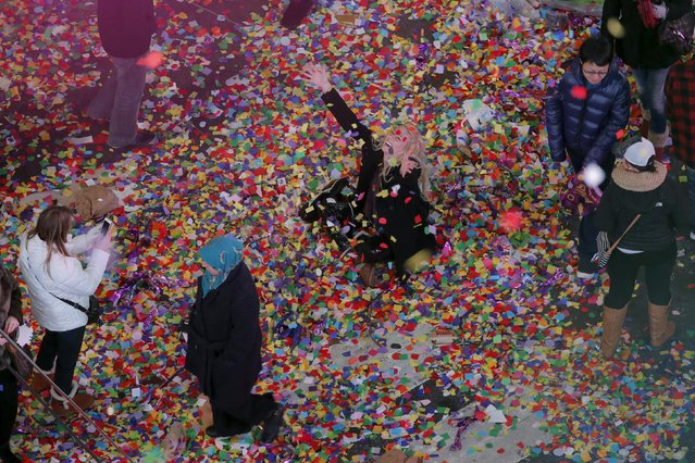 A reveler plays in confetti on the streets during New Year's festivities inside Times Square in New York January 1, 2016. (Photo by Lucas Jackson/Reuters)