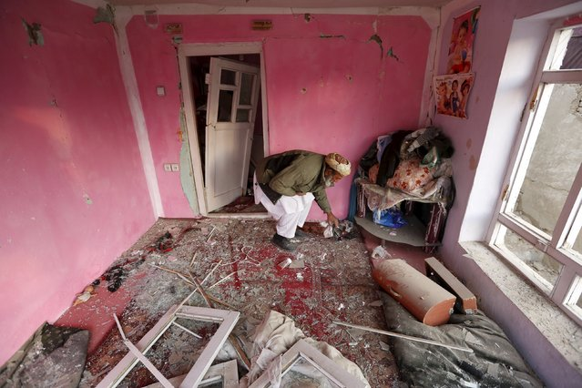"""An Afghan man removes broken glass in his house after a suicide attack  on French restaurant  """"Le Jardin"""" in Kabul, Afghanistan January 2, 2016. (Photo by Mohammad Ismail/Reuters)"""