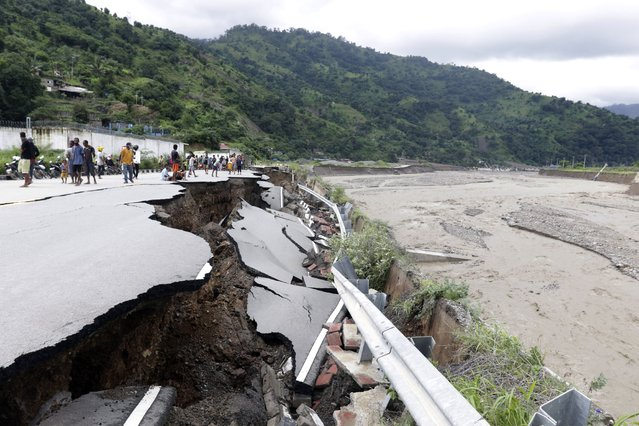 Residents inspect a damaged road following a flood in Dili, East Timor, Monday, April 5, 2021. (Photo by Kandhi Barnez/AP Photo)