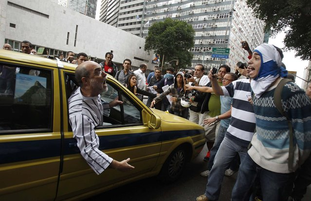 A passenger inside a taxi argues with a group of protesters who have blocked off an avenue during a demonstration against State Governor Sergio Cabral in downtown Rio de Janeiro, on August 15, 2013. (Photo by Pilar Olivares/Reuters)