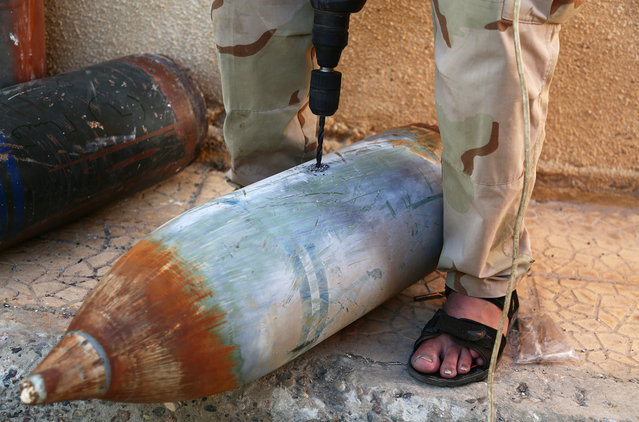 A rebel fighter drills into a bomb at a makeshift weapons workshop in the northern Syrian city of Raqqa, on August 5, 2013, where fighters recycle ordinance used by pro-government forces. (Photo by Mezar Matar/AFP Photo)