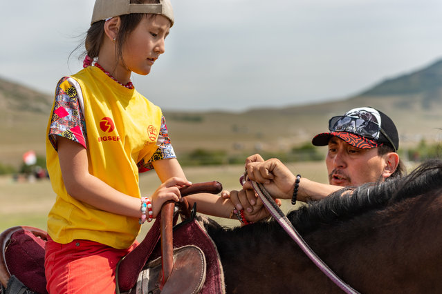 Ellana, eight, is coached by her father, Kostumov Farhat, on how to hold the reins to control her horse. Both her parents compete in the sport of archery – they say it's a great way for the family to be together and support one another. Ellana tells all her classmates and friends about her love for the sport and horses, which has inspired other young girls to become interested. (Photo by Eleanor Moseman/The Guardian)