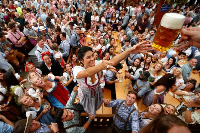A young woman receives a beer during the opening of the 185th 'Oktoberfest' beer festival in Munich, Germany, Saturday, September 22, 2018. The world's largest beer festival will be held from Sept. 22 until Oct. 7, 2018. (Photo by Matthias Schrader/AP Photo)
