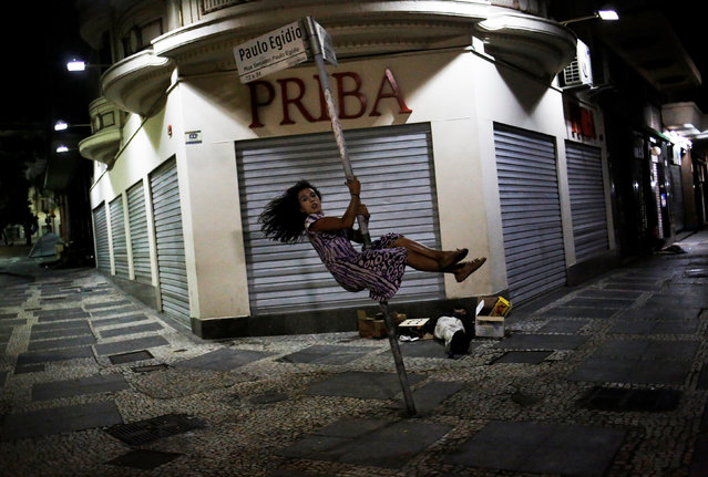 Safira, 25, who is among members of lesbian, gay, bisexual and transgender (LGBT) community, that have been invited to live in a building that the roofless movement has occupied, swings around a pole in Sao Paulo, Brazil, November 11, 2016. (Photo by Nacho Doce/Reuters)