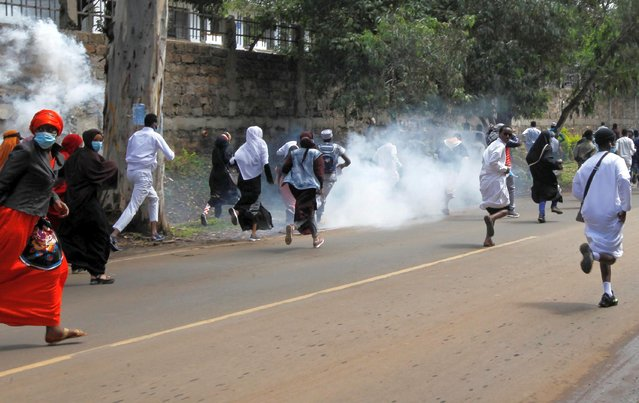 Pro-Palestinian demonstrators run past tear gas lobbed by riot policemen to disperse them during a protest following a flare-up of Israeli-Palestinian violence, in Nairobi, Kenya on May 13, 2021. (Photo by Monicah Mwangi/Reuters)