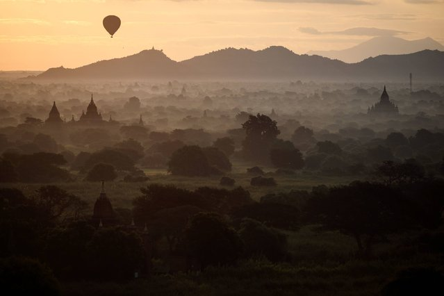 In this picture taken on November 28, 2016, a hot-air balloon carrying tourists sails over the archeological site at sunrise in Bagan. Located in central Myanmar, Bagan is home to more than 2,000 ancient Buddhist monuments deeply revered in the Buddhist-majority nation and is one of the country's most popular tourist destinations. (Photo by Dale De La Rey/AFP Photo)