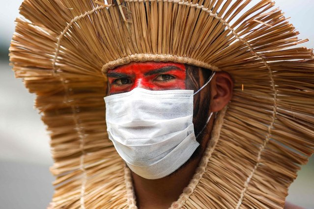 An indigenous man wears a protective mask during a protest against President Jair Bolsonaro's mining politics regarding indigenous lands, and demanding Brazilian Environment Minister Ricardo Salles' resignation, outside the Ministry of the Environment building in Brasilia on April 20, 2021, amid the COVID-19 pandemic. (Photo by Sergio Lima/AFP Photo)