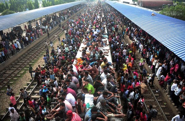 Bangladeshi Muslims travel on the roof of a train as they head to their homes ahead of Eid al-Adha as others wait at a railway station in Dhaka, Bangladesh, Tuesday, October 15, 2013. Hundreds of thousands of people working in Dhaka return home to spend time with their family during the Eid al-Adha celebrations. (Photo by AP Photo)