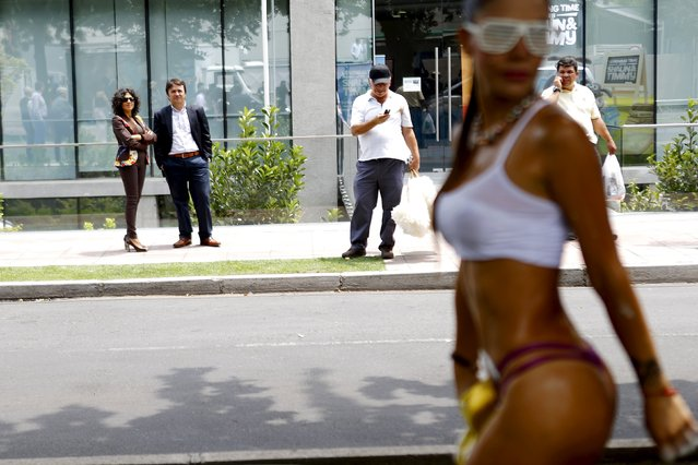 "An exotic dancer performs in a street during an ""Urban intervention"" publicity event for an adult club in Santiago, Chile, January 26, 2016. (Photo by Ivan Alvarado/Reuters)"