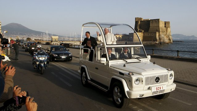 Pope Francis waves from the Popemobile as it drives on the seafront during his pastoral visit in Naples March 21, 2015. (Photo by Ciro De Luca/Reuters)