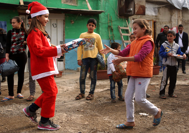 "Chloe, a Lebanese Christian teenager dressed as Santa Claus, hands a gift to a Syrian refugee on December 24, 2016 during a gift distribution organised by the maronite congregation ""Mission de Vie"" in a slum in the town of Dbayeh, north of Beirut. (Photo by Patrick Baz/AFP Photo)"