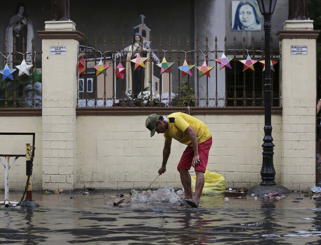 A man cleans the trash along a flooded area outside a church caused by rains from Typhoon Nock-Ten in Quezon city, north of Manila, Philippines on Monday, December 26, 2016. The powerful typhoon slammed into the eastern Philippines on Christmas Day, spoiling the biggest holiday in Asia's largest Catholic nation, where a governor offered roast pig to entice villagers to abandon family celebrations for emergency shelters. (Photo by Aaron Favila/AP Photo)