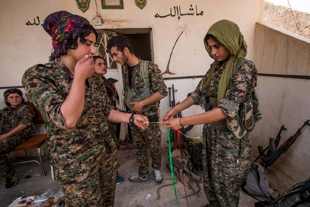 Kurdish female fighters from the People's Protection Units (YPG) weave together ribbons, bearing the colours of the YPG flag, in the Assyrian village of Tel Nasri, western of Tel Tamr town, after they said they retook control of the area from the Islamic State, May 21, 2015. (Photo by Rodi Said/Reuters)