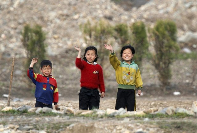 North Korean children wave to people on a Chinese tourist boat on the banks of Yalu River near the Chongsong county of North Korea, opposite the Chinese border city of Dandong, May 8, 2011. (Photo by Jacky Chen/Reuters)