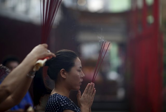 A woman prays with joss sticks at Dharma Bhakti Temple on the first day of the Lunar New Year in Jakarta, Indonesia February 8, 2016. (Photo by Darren Whiteside/Reuters)