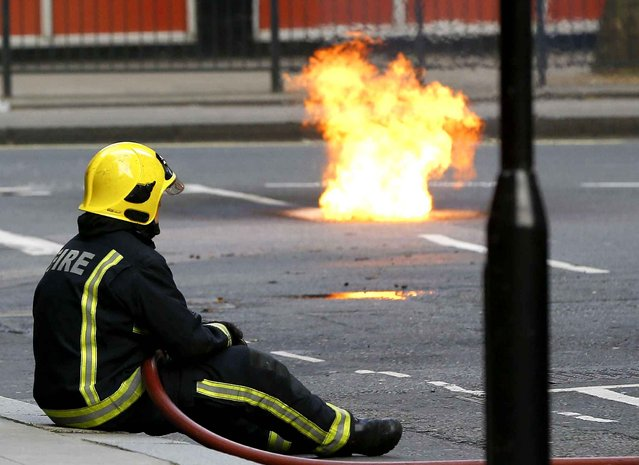 A fireman watches as flames come out of a manhole cover in the road, an electrical fire under the pavement near Holborn in London, Wednesday, April 1, 2015. People have been evacuated from nearby buildings. (Photo by Kirsty Wigglesworth/AP Photo)