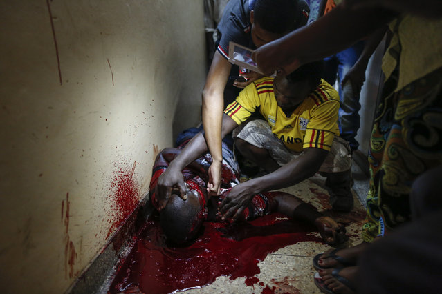 A supporter of Kizza Besigye, the leader of the main opposition Forum for Democratic Change (FDC) and the main opposition candidate, lays unconcious in his own blood after being shot by the police, as his friends claim, during a running battle between opposition supporters and police in Kampala, Uganda, 15 February 2016. Ugandan police used force to disperse and arrest opposition supporters on 15 February, detaining Besigye briefly before releasing him from custody.  (Photo by Dai Kurokawa/EPA)