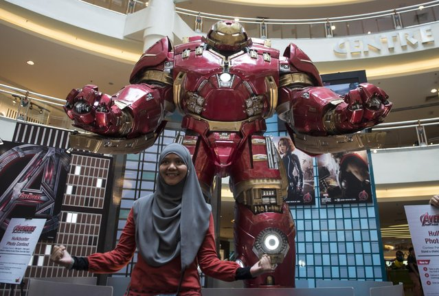A Malaysian Muslim woman poses with a Hulkbuster statue at a Avengers: Age of Ultron roadshow in a mall downtown Kuala Lumpur, Malaysia on Friday, April 10, 2015. The Avengers: Age of Ultron premieres in Malaysia on April 23. (Photo by Joshua Paul/AP Photo)