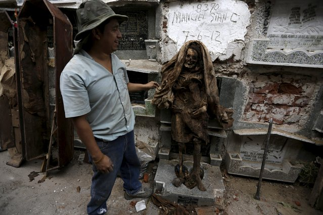 A grave cleaner touches a mummified body during exhumation work at the General Cemetery in Guatemala City, April 15, 2015. (Photo by Jorge Dan Lopez/Reuters)