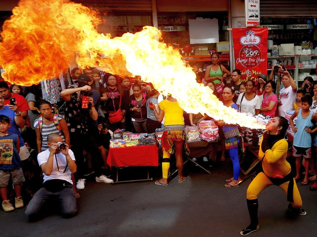 In this Tuesday, February 5, 2019, photo, fire-eater performs during celebrations of the Lunar New Year in the Chinatown district of Manila, Philippines. This year is the Year of the Earth Pig in the Chinese Lunar calendar and is supposed to represent abundance, diligence and generosity. (Photo by Bullit Marquez/AP Photo)