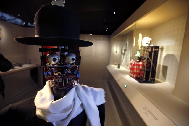 "The Berenson robot strolls among visitors during the exhibition ""Persona : Oddly Human"" at the Quai Branly museum in Paris, France, February 23, 2016. The Berenson robot, developed in France in 2011, is the brainchild of anthropologist Denis Vidal and robotics engineer Philippe Gaussier. Its programming allows it to record reactions of museum visitors to certain pieces of art and then use the data to develop its own unique taste, which allows ""Berenson"" to judge whether or not it likes a certain work of art within an exhibition. (Photo by Philippe Wojazer/Reuters)"