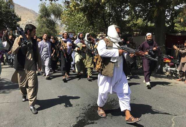 Taliban soldiers walk towards Afghans shouting slogans, during an anti-Pakistan demonstration, near the Pakistan embassy in Kabul, Afghanistan, Tuesday, September 7, 2021. (Photo by Wali Sabawoon/AP Photo)