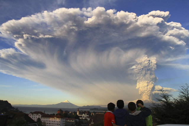 Children watch the Calbuco volcano erupt, from Puerto Varas, Chile, Wednesday, April 22, 2015. The volcano erupted billowing a huge ash cloud over a sparsely populated, mountainous area in southern Chile. Authorities ordered the evacuation of the inhabitants of the nearby town of Ensenada, along with residents of two smaller communities. (Photo by Carlos F. Gutierrez/AP Photo)