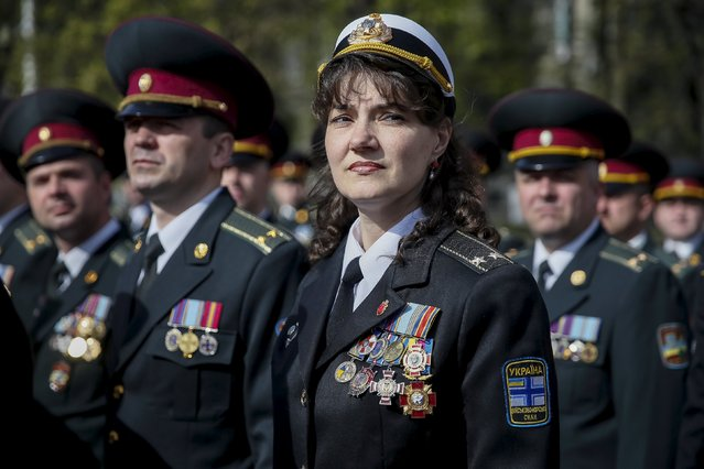 Ukrainian Navy officer (C) and army officers attend a graduation ceremony at the National University of Defence of Ukraine in Kiev, April 24, 2015. (Photo by Gleb Garanich/Reuters)
