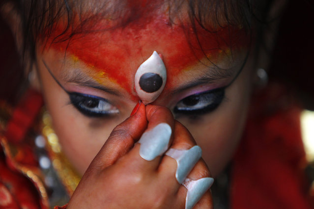 Nepal's Kumari, or living goddess, adjusts her ornament as she watches the Rato Machindranath chariot Festival in Lalitpur, Nepal, Friday, April 24, 2015. Nepal's living goddesses are young pre-pubescent girls considered by devotees to be incarnations of a Hindu goddess. Selected as toddlers, living goddesses usually keep their positions until they reach puberty. (Photo by Niranjan Shrestha/AP Photo)