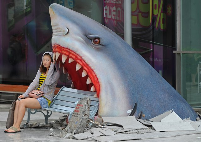 A foreign tourist sits next to a large art display of a shark displayed at a shopping mall in Bangkok on July 9, 2012. (Photo by Pornchai Kittiwongsakul/AFP Photo)