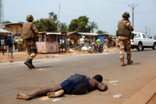 The body of a man who was killed by a mob that believed him to be a Seleka Muslim militia member lies on the ground near the PK11 checkpoint as French soldiers walk by in Bangui, Central African Republic, Friday, January 24, 2014. Christian militiamen killed a prominent Muslim former government minister who supported last year's rebellion, officials said, raising the specter of further sectarian bloodshed as tensions deepened Friday. (Photo by Jerome Delay/AP Photo)