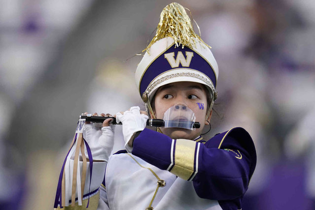 A piccolo player with the Washington Marching Band performs with a mouth shield due to the COVID-19 pandemic before an NCAA college football game against California, Saturday, September 25, 2021, in Seattle. (Photo by Elaine Thompson/AP Photo)