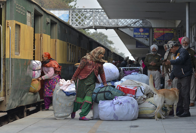 Passengers from Pakistan unload their belongings from the Samjhauta Express train as it arrives in Atari, India, Monday, March 4, 2019. A Pakistani railway official said the key train service with neighboring India has resumed in another sign of easing tensions between the two nuclear-armed rivals since a major escalation last week over disputed Kashmir region. (Photo by Prabhjot Gill/AP Photo)
