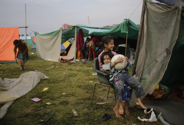 Survivors of Saturday's earthquake play outside their tent at a makeshift camp in Kathmandu, Nepal, Tuesday, April 28, 2015. (Photo by Altaf Qadri/AP Photo)